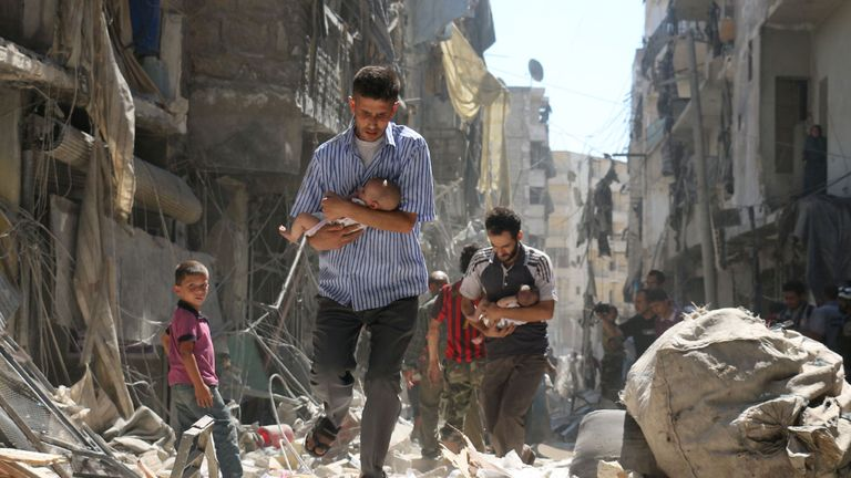 Syrian men carry babies through the rubble after an air strike on a rebel-held district of Aleppo
