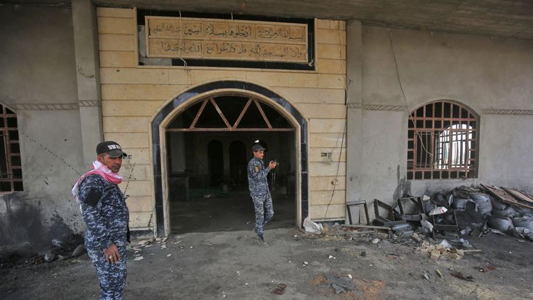 Iraqi forces examine a damaged mosque in the Shura district