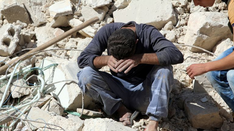 A man sits distraught after losing relatives in an airstrike in the besieged rebel-held al-Qaterji neighbourhood