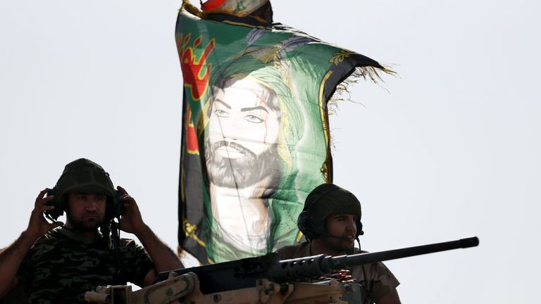 Iraqi special forces soldiers sit on top of an armoured vehicle next to a flag of Imam Hussein in Bartella