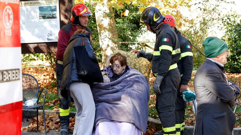 A woman is treated by rescuers in Norcia