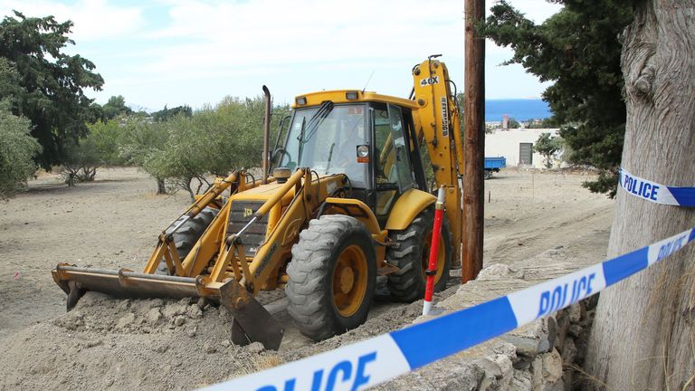 Police use a digger to search an olive grove near the farmhouse