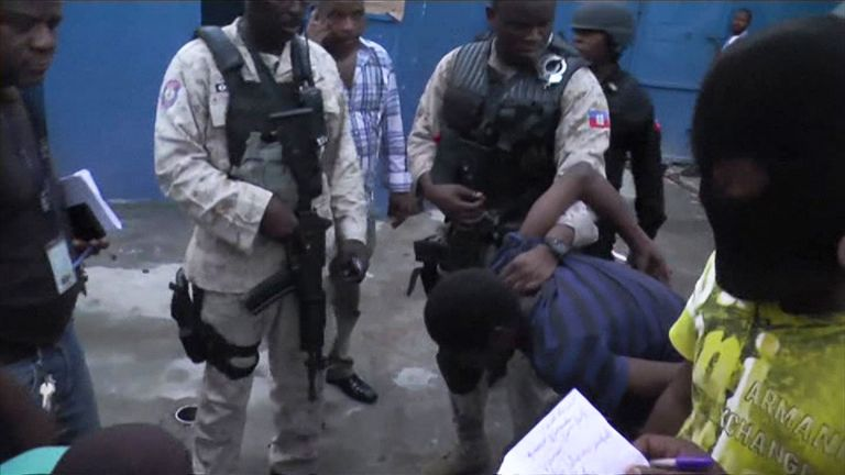 Security forces hold an inmate caught shortly after escaping the prison