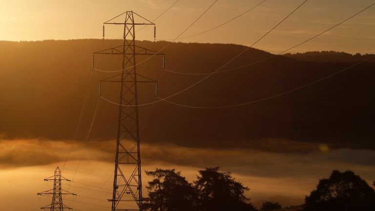An autumn mist sits behind electrical pylons on the River Tummel near Pitlochry in Perthshire