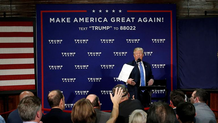Donald Trump tosses a paper after reading poll results in New Hampshire