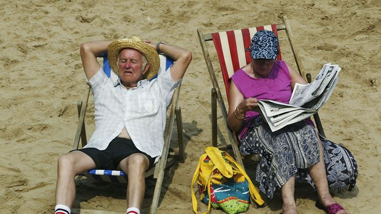 BLACKPOOL, ENGLAND - AUGUST 6: An elderly couple soak up the sun on Blackpool beach August 6, 2003 in Blackpool, England. The temperature in the UK peaked at 35.9 degrees Celsius today, making it the hottest day of the year so far. (Photo by Michael Steele/Getty Images)