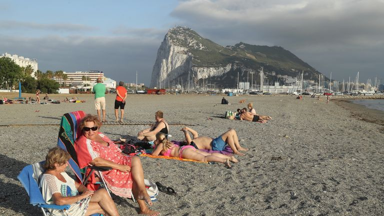 LA LINEA DE LA CONCEPCION, SPAIN - JUNE 22: Beachgoers lie in the sand as the British territory of Gibraltar looms behind the day before the EU Referendum on June 22, 2016 in La Linea de la Concepcion, Spain. Citizens of the United Kingdom and its territories will go to the polls tomorrow in what many expect to be a very tight vote on whether to remain in or leave the European Union. A result is expected early Friday morning. (Photo by Sean Gallup/Getty Images)