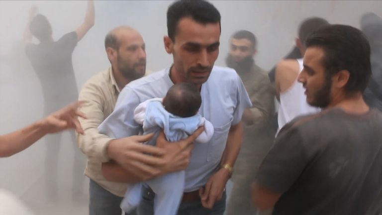 A man carries a baby away from a bombed area of Aleppo