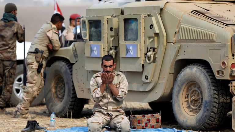 A member of Iraqi army prays after the liberation of Khalidiya village from Islamic State militants south of Mosul