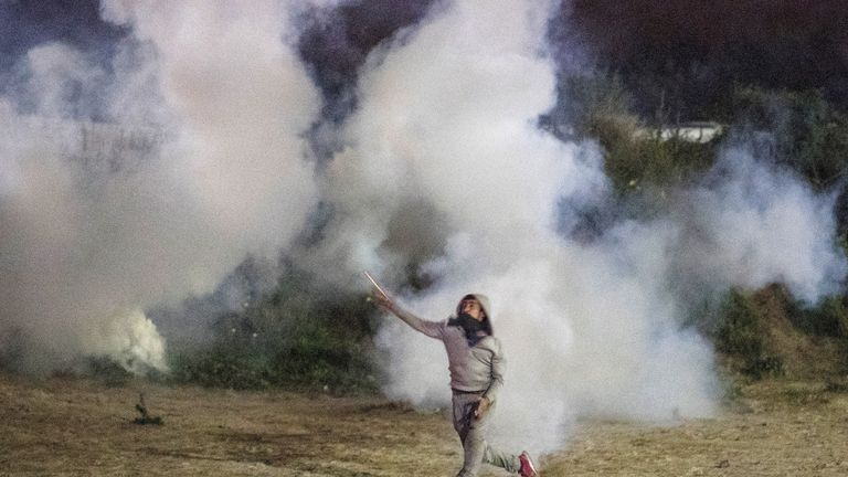 A migrant is is surrounded by tear gas as he throws stones at French riot police