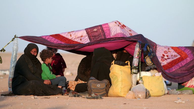 Iraqis who fled violence in Mosul rest under a makshift tent upon reaching Syria, near the Iraqi border, in Hasaka Governorate