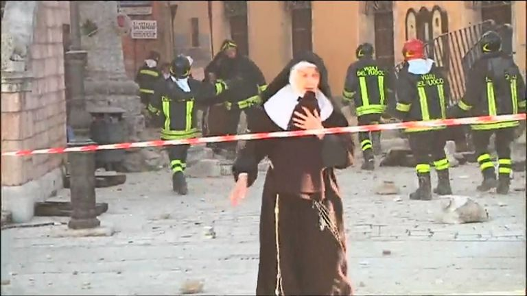 Rescue workers help as nuns flee from damaged buildings in Norcia