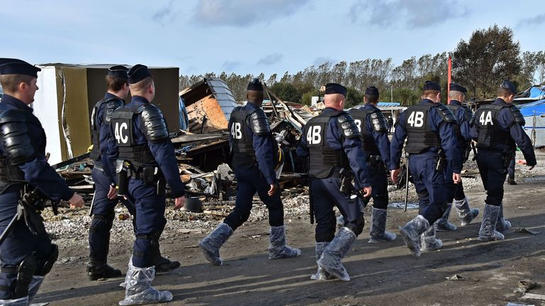 French policemen wearing boots protected with plastic walk through the camp