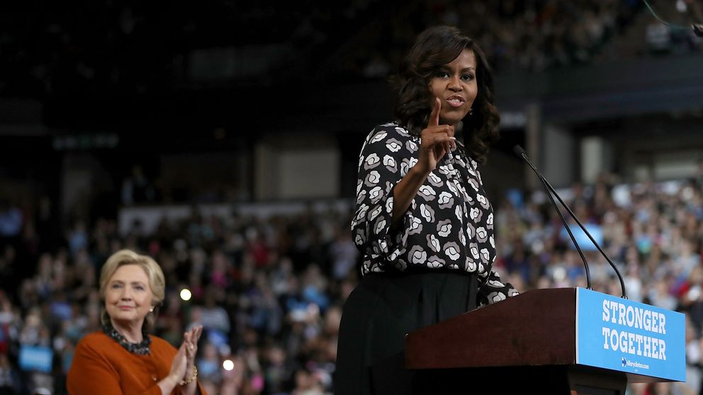 WINSTON-SALEM, NC - OCTOBER 27: Democratic presidential nominee former Secretary of State Hillary Clinton (L) looks on as First Lady Michelle Obama speaks during a campaign rally at Wake Forest University on October 27, 2016 in Winston-Salem, North Carolina. With less than two weeks to go before the election, Hillary Clinton is campaigning in North Carolina with First Lady Michelle Obama. (Photo by Justin Sullivan/Getty Images)