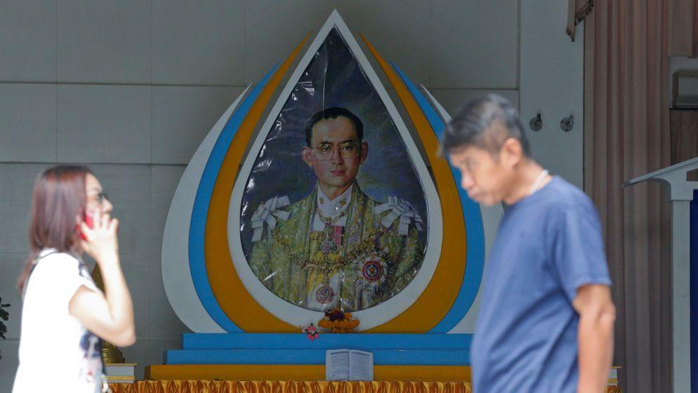 People walk past a picture of King Bhumibol Adulyadej at Siriraj Hospital