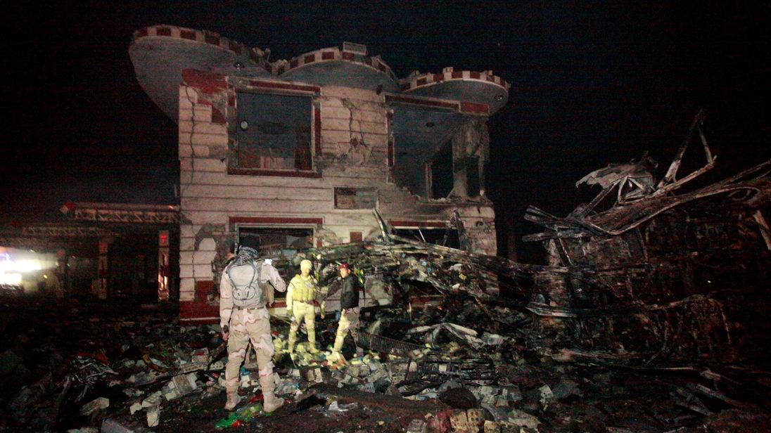 Iraqi security forces inspect the site of the blast