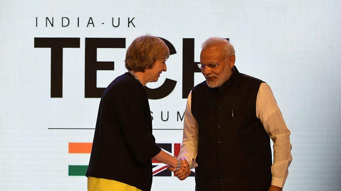 Theresa May shakes hands with Narendra Modi in Delhi