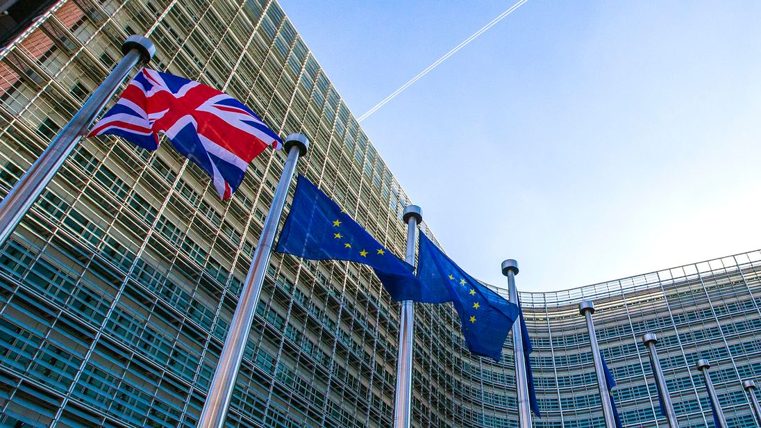 A Union Jack flag is seen next to European Union flags