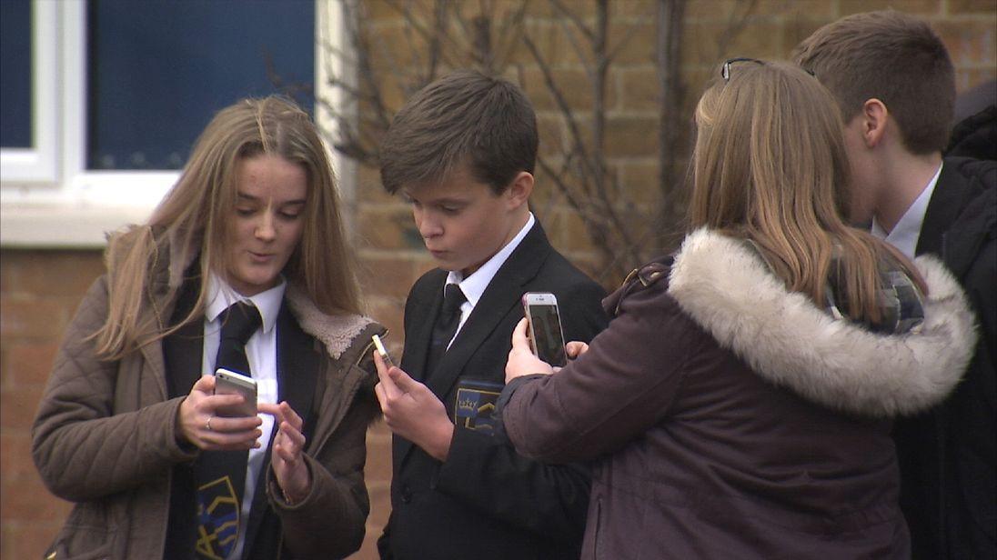 Children looking at mobile phones
