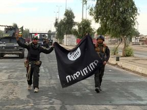 Two Iraqi soldiers carry a captured Islamic State flag