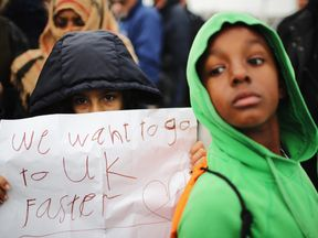 Women and children protest their case to the UK goverment at the Jungle camp as migrants leave and the authorities demolish the site on October 26, 2016 in Calais