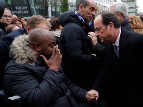 President Hollande greets a victim of the Paris attacks
