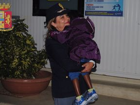 Police officer Maria Volpe with Oumoh, 4, a young Ivoirian migrant
