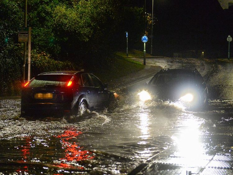 Cars drive through flash flooding in Plympton, Devon. Pic: Matt Gilley