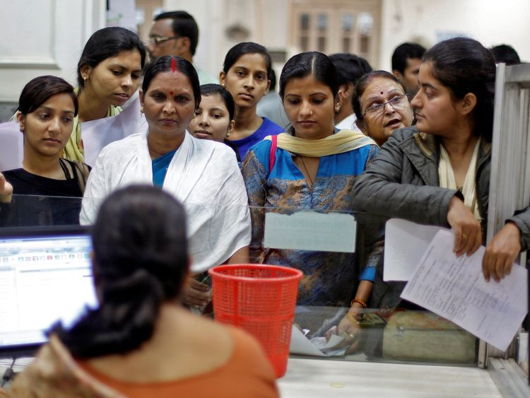 People queue to deposit RUPEE banknotes inside a bank in Allahabad