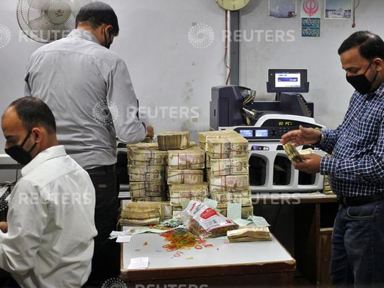 Bank employees count old 500 Indian rupee banknotes inside a bank in Jammu