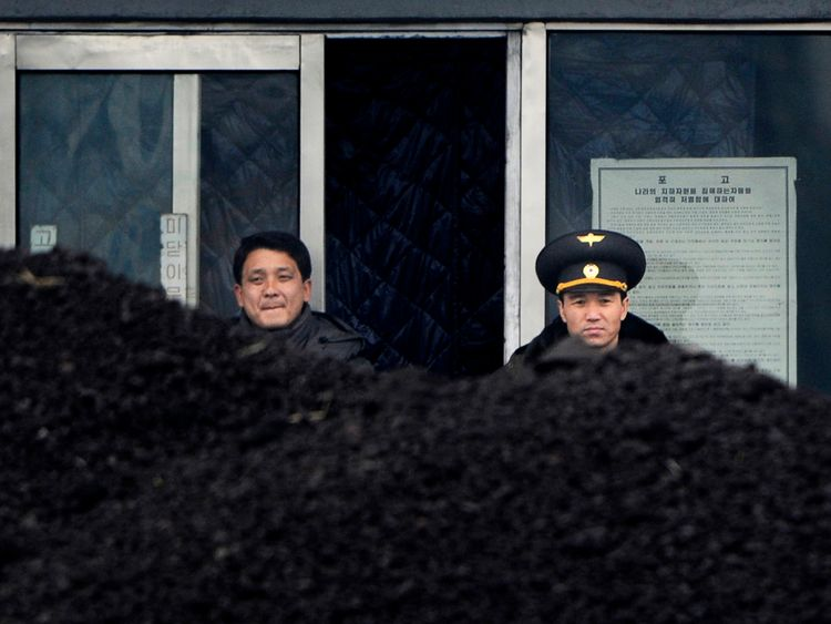 This picture taken on December 14, 2012 from China's northeastern city of Dandong, looking across the border, shows a North Korean military officer (R) and a North Korea man (L) standing behind a pile of coal along the banks of the Yalu River in the northeast of the North Korean border town of Siniuju. China is North Korea's biggest trading partner by far, and most of the business passes through Dandong in northeastern China, where lorries piled high with tyres and sacks are processed at the cus
