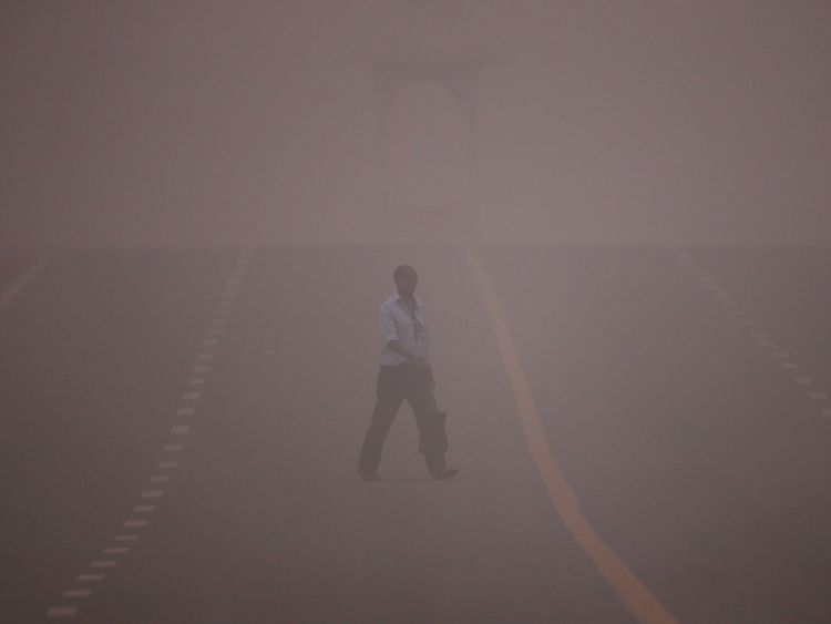 A man crosses a road amidst the heavy smog in New Delhi