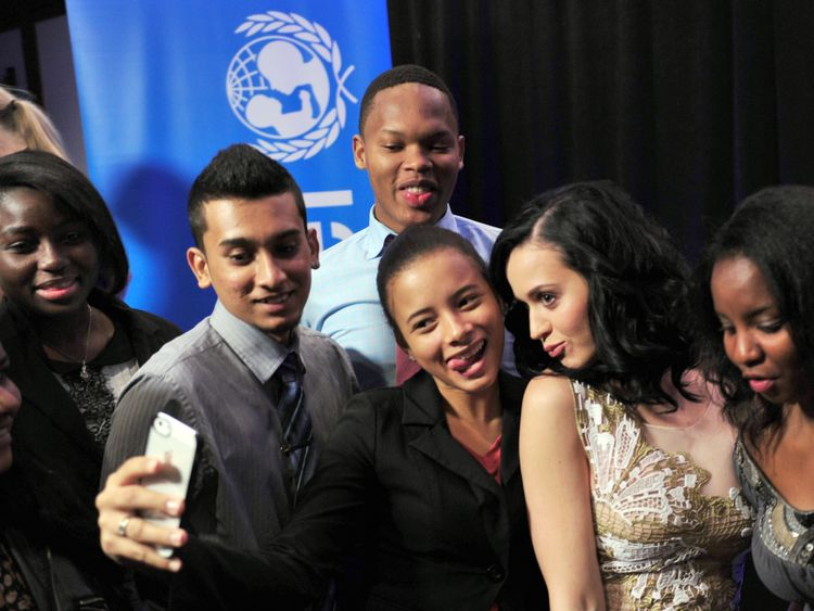 US singer Katy Perry (2nd R) poses with local students after being named a UNICEF goodwill ambassador December 3, 2013 at UNICEF headquarters in New York. AFP PHOTO/Stan HONDA (Photo credit should read STAN HONDA/AFP/Getty Images)