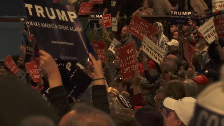 Donald Trump supporters wave placards at a rally