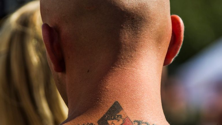 A man wears a white power tattoo on his neck while attending a neo-Nazi meeting in Germany