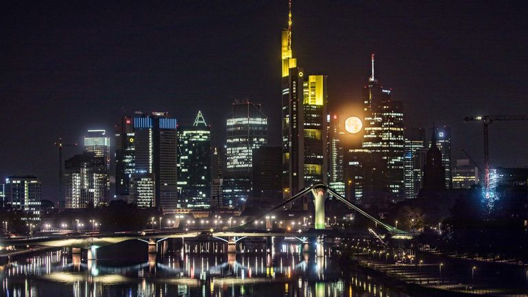 Full moon sets behind the banking district in Frankfurt am Main, western Germany