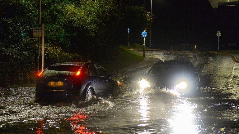 Cars drive through flash flooding in Plympton, Devon. Pic: Matt Gilley