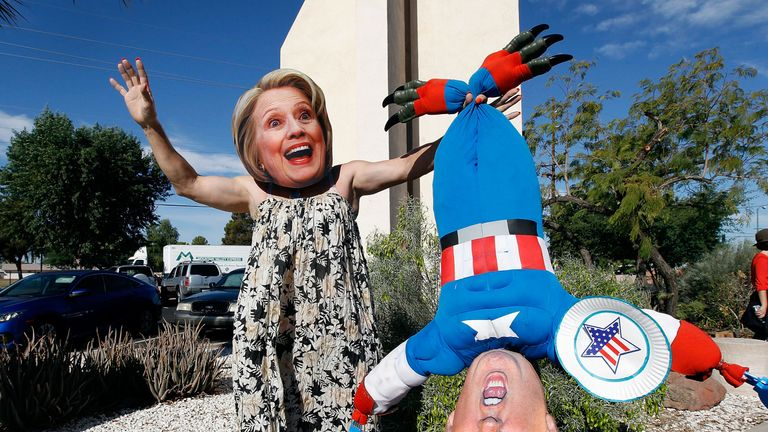 Phoenix, Arizona: Hillary Clinton supporter Jorge Mendez wears a dress and Hillary Clinton mask while holding a makeshift doll of Donald Trump after casting his vote