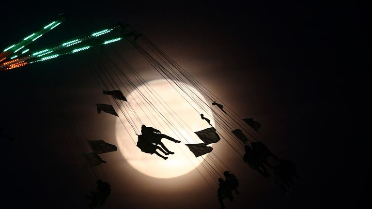 """People on a funfair ride are silhouetted against the moon a day before the """"supermoon"""" spectacle, in London, Britain November 13, 2016"""
