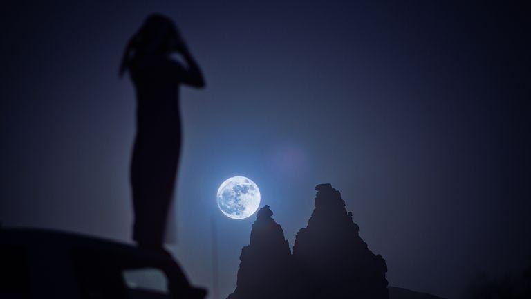A woman looks at the 'supermoon' rising over the desert near Tabuk in Saudi Arabia