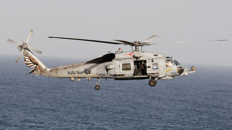 A Sikorsky SH-60 Seahawk helicopter flies near the Nimitz-class aircraft carrier USS Abraham Lincoln during a transit through the Strait of Hormuz, February 14, 2012