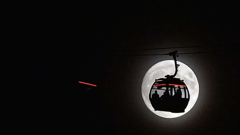 The moon rises behind clouds as the Emirates Air Line cable car is pictured in London's Docklands on November 13, 2016. Tomorrow, the moon will orbit closer to the earth than at any time since 1948, named a 'supermoon', it is defined by a Full or New moon coinciding with the moon's closest approach to the Earth