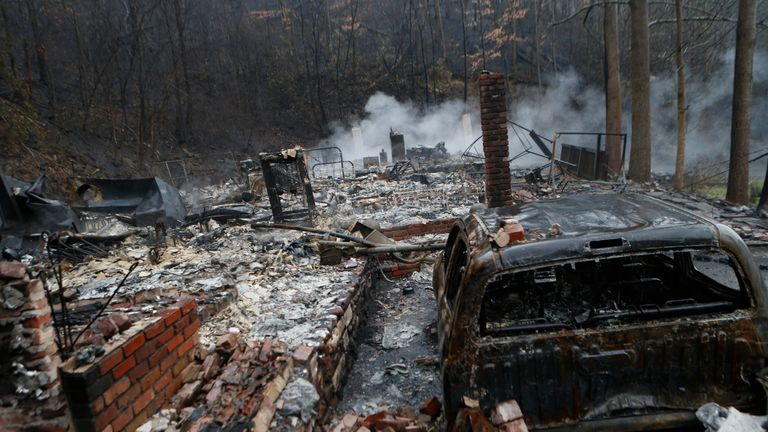 GATLINBURG, TN - NOVEMBER 30: The remains of a home smolder in the wake of a wildfire November 30, 2016 in Gatlinburg, Tennessee. Thousands of people have been evacuated from the area and over 100 houses and businesses were damaged or destroyed. Drought conditions and high winds helped the fire spread through the foothills of the Great Smoky Mountains. (Photo by Brian Blanco/Getty Images)
