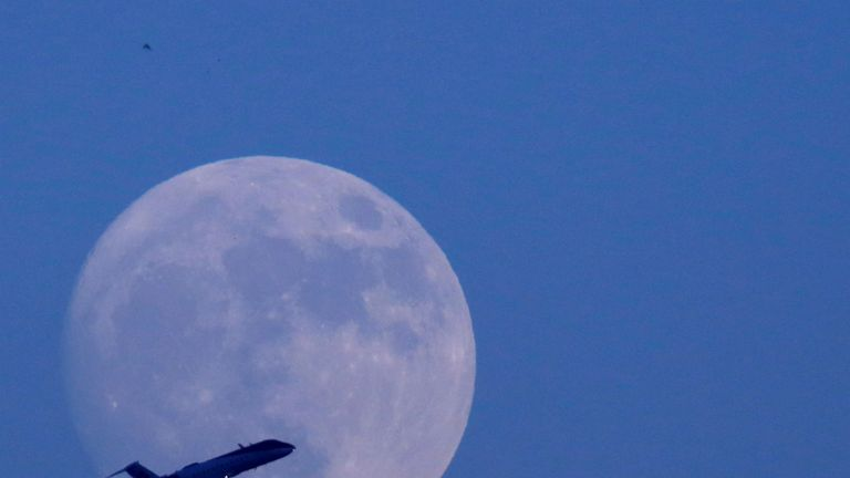 """A plane flies past the moon a day before the """"supermoon"""" spectacle in Kathmandu, Nepal November 13, 2016"""