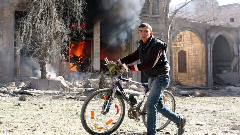 A Syrian youth pushes his bicycle past a burning house on November 19, 2016 following a reported air strike on Aleppo's rebel-held neighbourhood of Bab al-Nayrab. Intense government air strikes and artillery fire killed at least 27 people in rebel-held parts of Syria's Aleppo, where hospitals have been destroyed and schools forced to close. / AFP / AMEER ALHALBI (Photo credit should read AMEER ALHALBI/AFP/Getty Images)