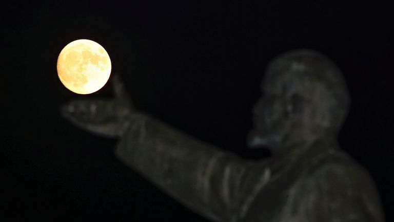 """A full moon rises behind a statue of Soviet state founder Vladimir Lenin on the eve of the """"supermoon"""" spectacle, Baikonur, Kazakhstan, November 13, 2016"""