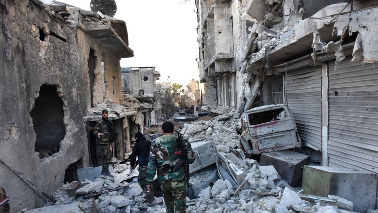 Syrian pro-government forces walk amidst heavy destruction in Aleppo's Bustan al-Basha neighbourhood on November 28, 2016, during their assault to retake the entire northern city from rebel fighters. In a major breakthrough in the push to retake the whole city, regime forces captured six rebel-held districts of eastern Aleppo over the weekend, including Masaken Hanano, the biggest of those in eastern Aleppo. / AFP / GEORGE OURFALIAN (Photo credit should read GEORGE OURFALIAN/AFP/Getty Images)