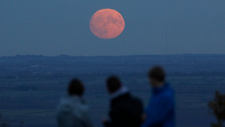 """A family watch the moon rise a day before the """"supermoon"""" spectacle on Beacon Hill near Loughborough, Britain, November 13, 2016"""