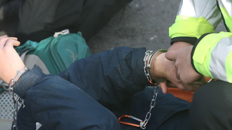 Police place handcuffs on a protestor from campaign group RisingUp! as they block the east ramp at Heathrow Airport, in protest over the development of a third runway. PRESS ASSOCIATION Photo. Picture date: Saturday November 19, 2016. See PA story PROTEST Heathrow. Photo credit should read: Steve Parsons/PA Wire