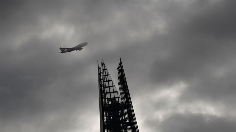 A plane flies past The Shard in London. File picture